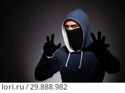 Young gangster in hood on grey background. Стоковое фото, фотограф Elnur / Фотобанк Лори