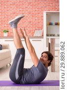 Купить «Young handsome man doing sport exercises at home», фото № 29889062, снято 12 сентября 2018 г. (c) Elnur / Фотобанк Лори