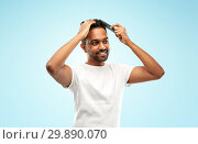 Купить «happy indian man brushing hair with comb», фото № 29890070, снято 27 октября 2018 г. (c) Syda Productions / Фотобанк Лори