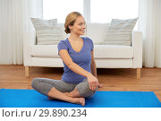 Купить «woman doing twist in lotus pose at home», фото № 29890234, снято 13 ноября 2015 г. (c) Syda Productions / Фотобанк Лори