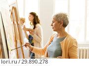 Купить «senior woman painting at art school studio», фото № 29890278, снято 26 мая 2017 г. (c) Syda Productions / Фотобанк Лори