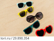 Купить «different sunglasses on beach sand», фото № 29890354, снято 27 июня 2018 г. (c) Syda Productions / Фотобанк Лори