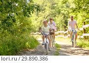 Купить «happy family riding bicycles in summer park», фото № 29890386, снято 15 июля 2018 г. (c) Syda Productions / Фотобанк Лори