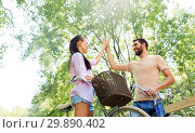 Купить «couple with bicycles making high five in summer», фото № 29890402, снято 15 июля 2018 г. (c) Syda Productions / Фотобанк Лори