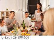 Купить «happy family having dinner party at home», фото № 29890666, снято 15 декабря 2018 г. (c) Syda Productions / Фотобанк Лори