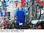 Купить «Male seller in uniform working in sport hypermarket», фото № 29890774, снято 27 сентября 2016 г. (c) Яков Филимонов / Фотобанк Лори