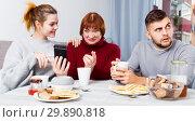 Купить «Man bored while wife and mother looking at phones», фото № 29890818, снято 27 ноября 2017 г. (c) Яков Филимонов / Фотобанк Лори