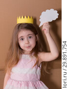Close up portrait little girl with a crown standing isolated over gray cardboard background holding speech bubble. Looking camera. space for text. Стоковое фото, фотограф Константин Сиятский / Фотобанк Лори