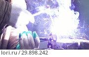 Купить «Industrial concept. A man welder working with a chain. Fire sparkles», видеоролик № 29898242, снято 9 апреля 2020 г. (c) Константин Шишкин / Фотобанк Лори