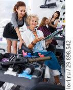 Купить «Elderly female with magazine discussing with hairdresser», фото № 29898542, снято 26 июня 2018 г. (c) Яков Филимонов / Фотобанк Лори