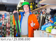 Купить «Portrait of adult man in jacket and helmet who is demonstrating ski in store.», фото № 29898690, снято 31 июля 2017 г. (c) Яков Филимонов / Фотобанк Лори
