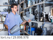 Купить «Male is choosing plastic trumpet in plumbing department», фото № 29898978, снято 26 июля 2017 г. (c) Яков Филимонов / Фотобанк Лори