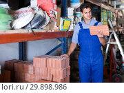Купить «concentrated male in uniform is choosing tile in the building store», фото № 29898986, снято 26 июля 2017 г. (c) Яков Филимонов / Фотобанк Лори