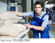 Купить «Shop assistant is checking bags with cement», фото № 29898994, снято 26 июля 2017 г. (c) Яков Филимонов / Фотобанк Лори