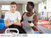 Купить «Male coach talking with upset teenage boy on gymnastic equipment at acrobatic center», фото № 29917686, снято 17 января 2019 г. (c) Яков Филимонов / Фотобанк Лори