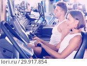 Man and woman workout using cycling cardio machines. Стоковое фото, фотограф Яков Филимонов / Фотобанк Лори