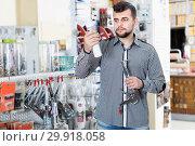Купить «Smiling man customer choosing new glue», фото № 29918058, снято 5 апреля 2017 г. (c) Яков Филимонов / Фотобанк Лори