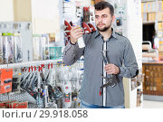 Smiling man customer choosing new glue. Стоковое фото, фотограф Яков Филимонов / Фотобанк Лори
