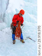 Mountaineer standing under the glacier is preparing a rope for climbing. Стоковое фото, фотограф Евгений Харитонов / Фотобанк Лори
