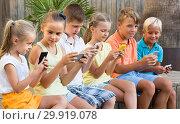 Купить «children in school age looking at mobile phones and sitting outdoors», фото № 29919078, снято 19 июня 2019 г. (c) Яков Филимонов / Фотобанк Лори