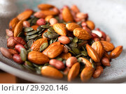 Купить «A mixture of wet washed nuts and seeds on the sieve. Peanuts, pumpkin seeds, almonds», фото № 29920146, снято 23 августа 2017 г. (c) katalinks / Фотобанк Лори
