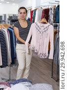 Купить «Woman holding and showing blouse on hanger», фото № 29942698, снято 10 октября 2018 г. (c) Яков Филимонов / Фотобанк Лори