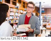 Купить «Handsome smiling guy getting acquainted with female student in bookstore», фото № 29951542, снято 18 января 2018 г. (c) Яков Филимонов / Фотобанк Лори