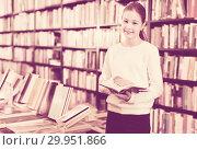 Купить «Intelligent preteen girl standing alone near bookcase in library browsing textbooks», фото № 29951866, снято 22 февраля 2018 г. (c) Яков Филимонов / Фотобанк Лори