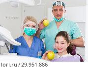 Купить «Confident dentists with smiling girl patient showing apples», фото № 29951886, снято 1 марта 2018 г. (c) Яков Филимонов / Фотобанк Лори