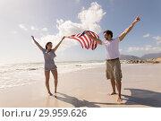 Купить «Happy young couple with arms outstretched holding american flag on beach», фото № 29959626, снято 6 ноября 2018 г. (c) Wavebreak Media / Фотобанк Лори