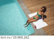 Купить «Young African American woman sitting at poolside in her backyard», фото № 29960262, снято 7 ноября 2018 г. (c) Wavebreak Media / Фотобанк Лори