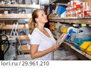 Купить «Portrait of young woman customer looking tools with note list in build store», фото № 29961210, снято 20 сентября 2018 г. (c) Яков Филимонов / Фотобанк Лори