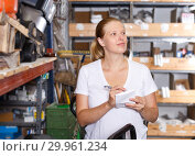 Купить «Woman holding shop list and choosing tools at shelves in build store», фото № 29961234, снято 20 сентября 2018 г. (c) Яков Филимонов / Фотобанк Лори