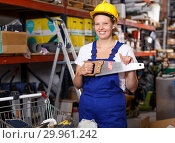 Купить «Young female in uniform and helmet holding saw near shelves with tools», фото № 29961242, снято 20 сентября 2018 г. (c) Яков Филимонов / Фотобанк Лори