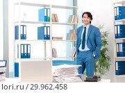 Купить «Young handsome male employee with too much work in the office», фото № 29962458, снято 10 ноября 2018 г. (c) Elnur / Фотобанк Лори