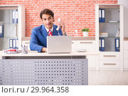 Купить «Young handsome employee working in the office», фото № 29964358, снято 12 сентября 2018 г. (c) Elnur / Фотобанк Лори