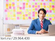 Купить «Young handsome employee with many conflicting priorities», фото № 29964430, снято 16 октября 2018 г. (c) Elnur / Фотобанк Лори