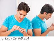 Купить «Man trying contact lenses at home», фото № 29969254, снято 6 августа 2018 г. (c) Elnur / Фотобанк Лори