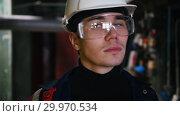 Купить «A young man engineer in protective glasses walking in manufacturing plant and looking around», видеоролик № 29970534, снято 16 февраля 2019 г. (c) Константин Шишкин / Фотобанк Лори