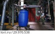 Купить «A man engineer in manufacturing plant rolls a cart with a barrel», видеоролик № 29970538, снято 16 февраля 2019 г. (c) Константин Шишкин / Фотобанк Лори