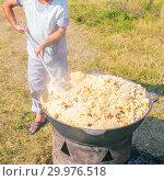 "Купить «Russia, Samara, August, 2018: Preparation of pilaf in a cauldron at the military-historical festival ""Military deed"".», фото № 29976518, снято 5 августа 2018 г. (c) Акиньшин Владимир / Фотобанк Лори"
