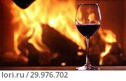 Купить «A man's hand pours red wine from a bottle into a glass on the background of a burning fireplace», видеоролик № 29976702, снято 15 февраля 2019 г. (c) Алексей Кузнецов / Фотобанк Лори