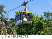 Купить «Sochi, Russia - June 5. 2018. People in cable car in the Arboretum», фото № 29976778, снято 5 июня 2018 г. (c) Володина Ольга / Фотобанк Лори