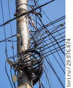Купить «Крепление кабелей к бетонному столбу в беспорядке», фото № 29976874, снято 19 августа 2018 г. (c) Вячеслав Палес / Фотобанк Лори