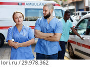Купить «Portrait of happy male and female paramedicals near ambulance car0», фото № 29978362, снято 30 ноября 2018 г. (c) Яков Филимонов / Фотобанк Лори