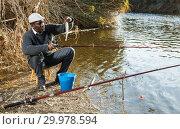 Купить «Man fishing with rods on river», фото № 29978594, снято 27 января 2019 г. (c) Яков Филимонов / Фотобанк Лори