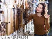 Купить «Woman showing different pendant», фото № 29978654, снято 27 апреля 2017 г. (c) Яков Филимонов / Фотобанк Лори