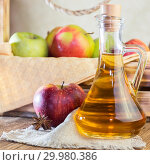 Купить «Processing of an agricultural crop of red and green apples. Homemade preparations, healthy diet vegetarian food. Spiced apple cider vinegar, juice, cider in a glass jug next to a box of ripe fruit», фото № 29980386, снято 16 февраля 2019 г. (c) Светлана Евграфова / Фотобанк Лори