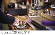 Купить «Barista making coffee. Stick out the holder and cleaning it», видеоролик № 29980518, снято 18 февраля 2019 г. (c) Константин Шишкин / Фотобанк Лори