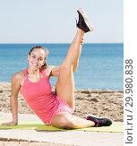 Купить «Smiling young woman training gymnastics at sea beach», фото № 29980838, снято 18 июля 2019 г. (c) Яков Филимонов / Фотобанк Лори